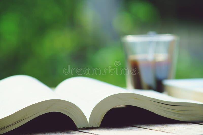 Pila de libro y taza de café en la tabla de madera en el color de tono del vintage, concepto de la sabiduría, espacio de la copia fotografía de archivo