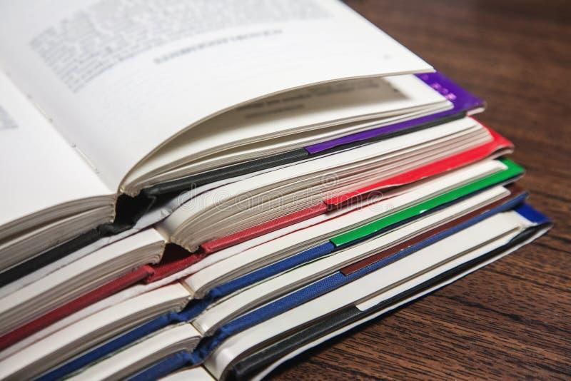 Pila de libros abiertos en la tabla de madera foto de archivo