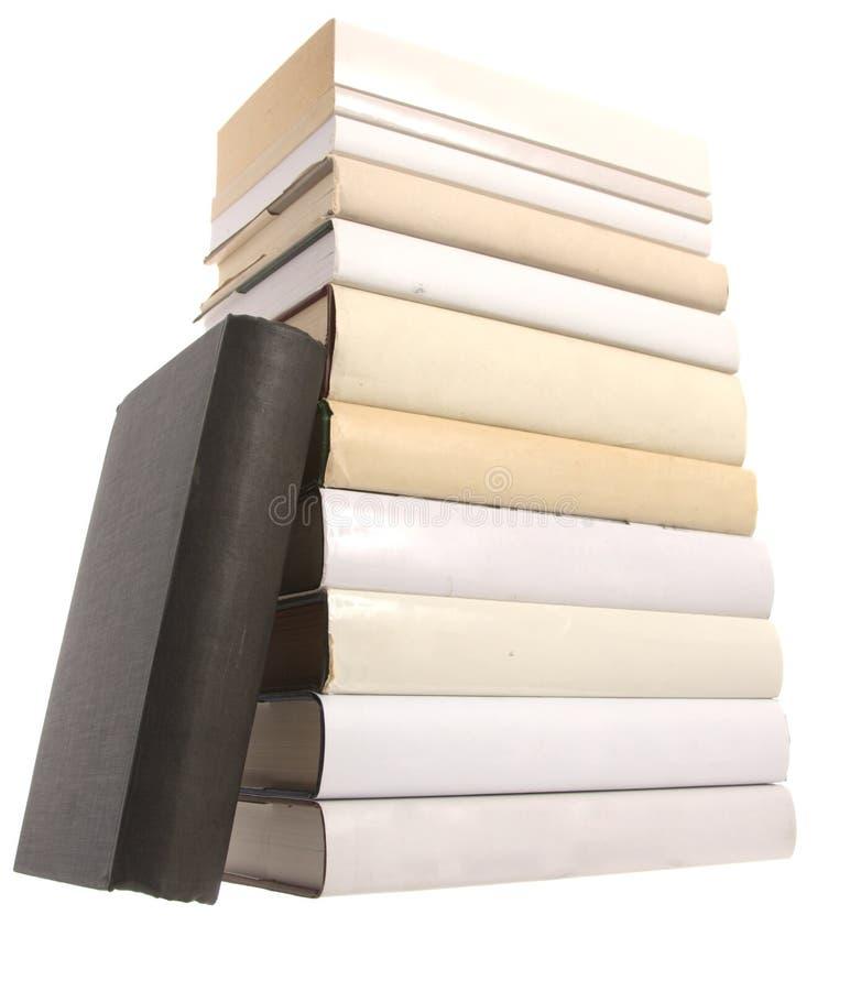 Pila de libros blancos con un libro negro fotos de archivo