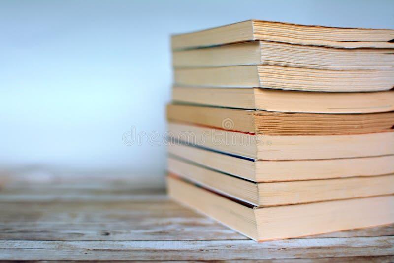 Pila de libros de bolsillo usados viejos amarilleados en el escritorio de madera y el fondo azul claro foto de archivo