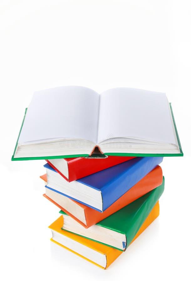 Pila de libros coloridos, un libro abierto de par en par en tapa foto de archivo libre de regalías
