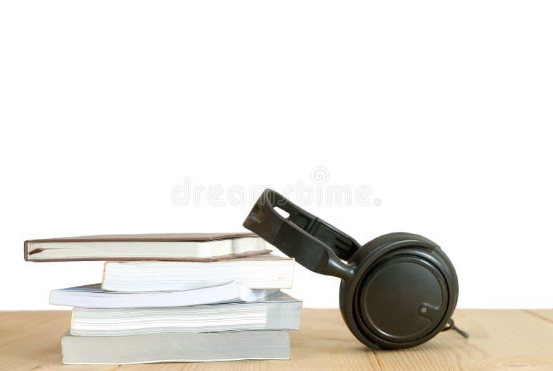 Pila de libros con el auricular en la tabla de madera imágenes de archivo libres de regalías