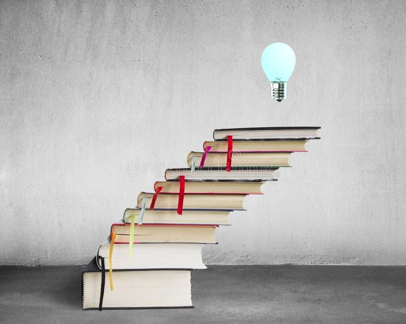 Pila de libros con la lámpara en el top imagenes de archivo