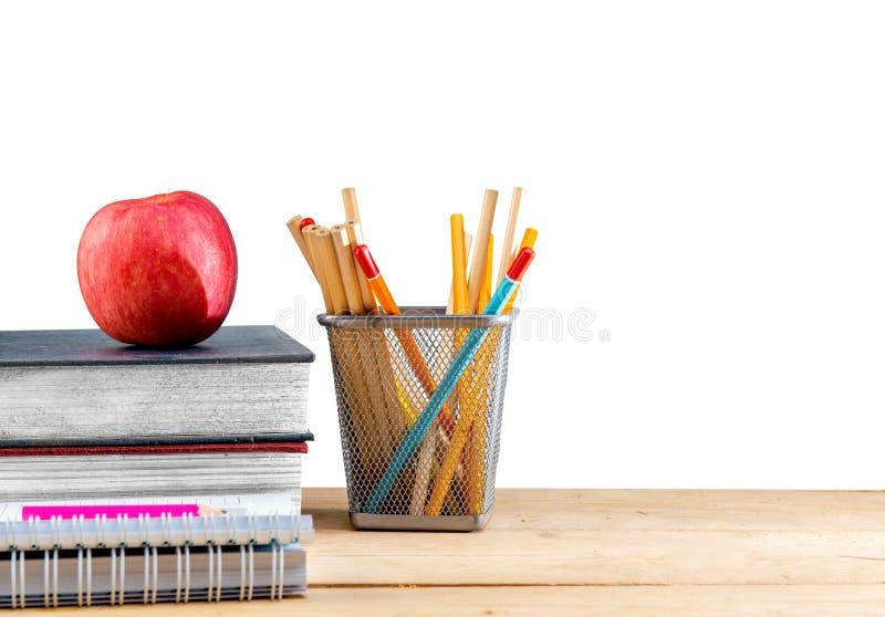Pila de libros con la manzana y de l?pices en envase de la cesta en la tabla de madera imagenes de archivo