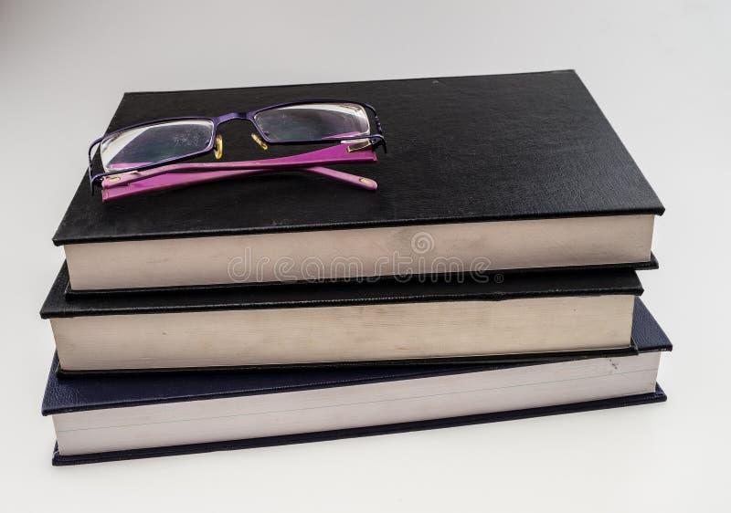 Pila de libros con un par de lentes imágenes de archivo libres de regalías