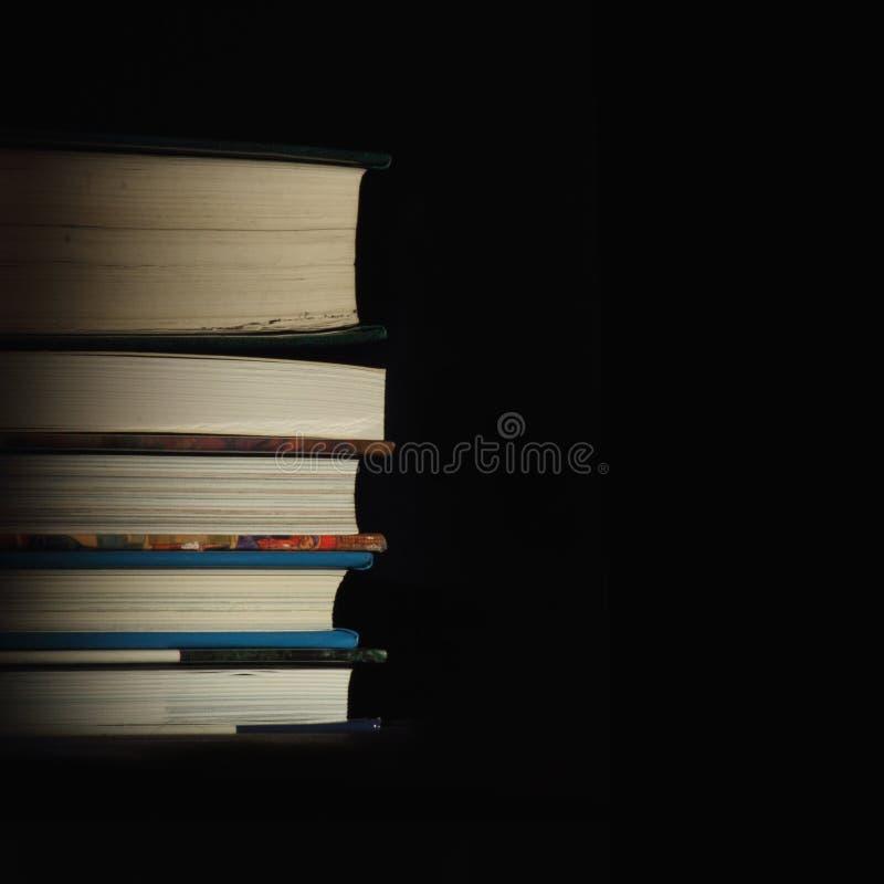 Pila de libros en el fondo negro foto de archivo libre de regalías