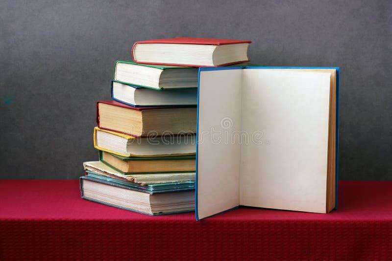Pila de libros en la tabla, un libro abierto foto de archivo libre de regalías