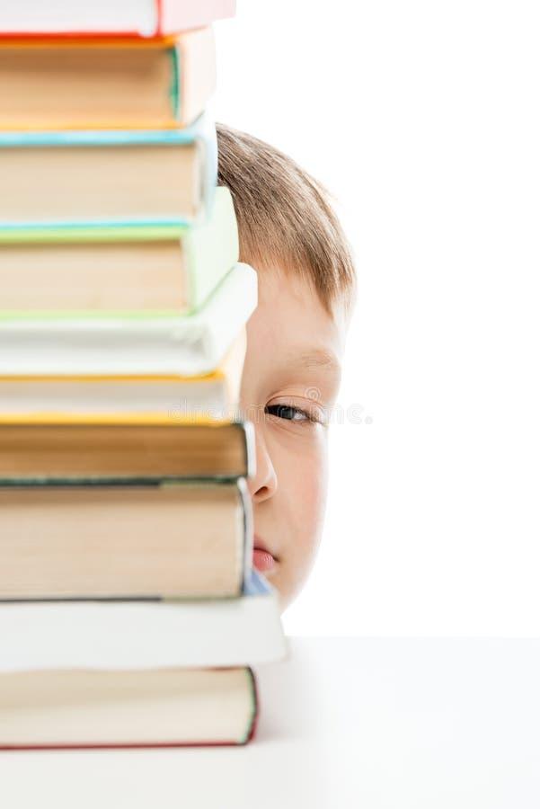 Pila de libros a leer en la tabla y la mirada furtiva hacia fuera de detrás t imagenes de archivo