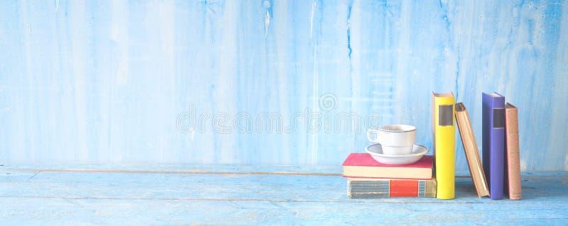 Pila de libros multicolores del libro encuadernado con una taza de café, educación de la lectura, literatura, espacio panorámico, foto de archivo