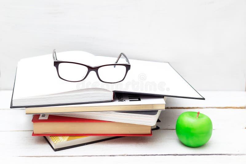 Pila de libros para el estudio y una manzana verde en un fondo blanco fotografía de archivo libre de regalías