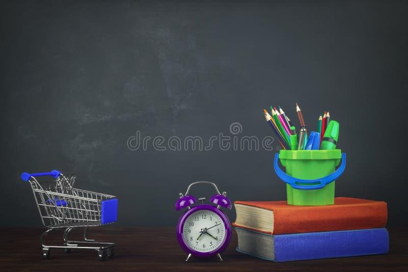 Pila de libros de texto coloridos en una tabla de madera, y carro del ultramarinos, efectos de escritorio y despertador De nuevo  fotos de archivo