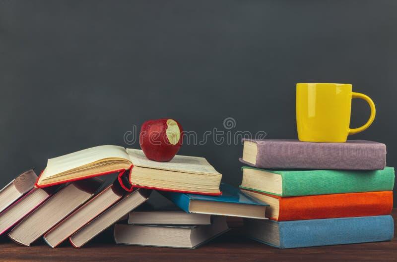 Pila de libros de texto multicolores en la tabla de madera, la taza de café y la manzana roja De nuevo a escuela fotos de archivo libres de regalías