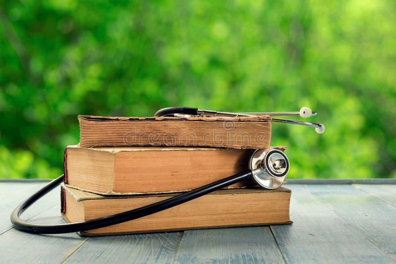 Pila de libros viejos con el estetoscopio en la tabla de madera imagen de archivo libre de regalías