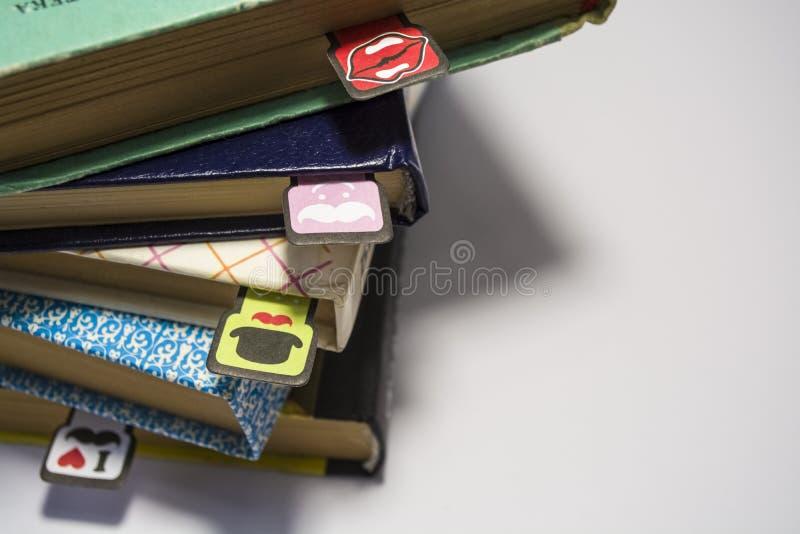 Pila de libros viejos con las hojas amarillas dadas vuelta en un fondo blanco Señales alegres con los bigotes de diverso colorant fotos de archivo libres de regalías