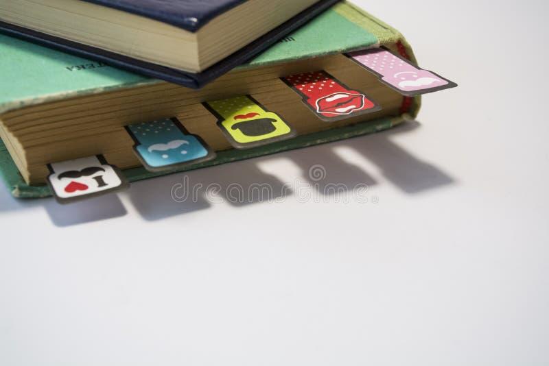 Pila de libros viejos con las hojas amarillas dadas vuelta en un fondo blanco Señales alegres con los bigotes de diverso colorant fotografía de archivo