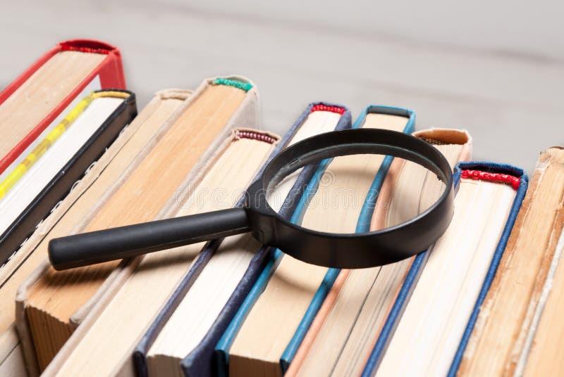 Pila de libros viejos del libro encuadernado con la lupa Busque para la información relevante y necesaria en un gran número de du imagen de archivo libre de regalías