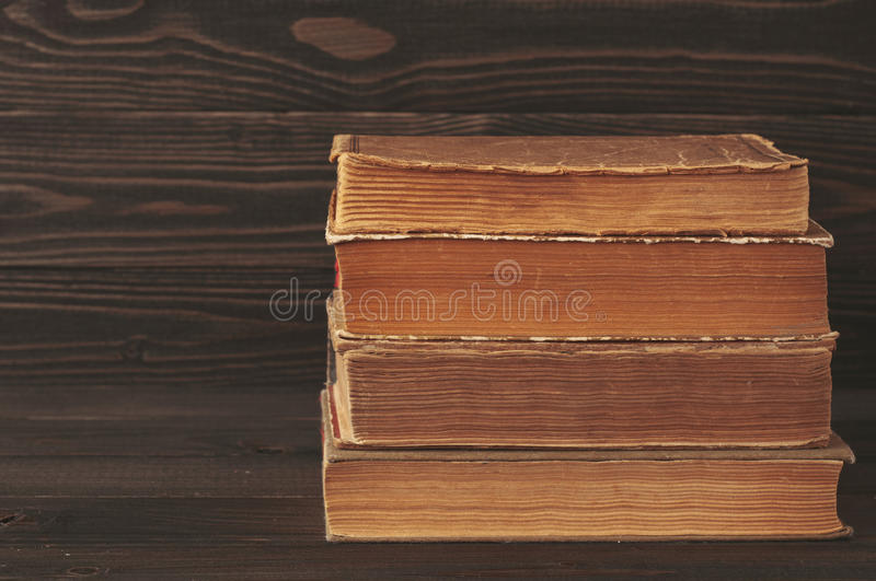 Pila de libros viejos en fondo de madera oscuro imagen de archivo