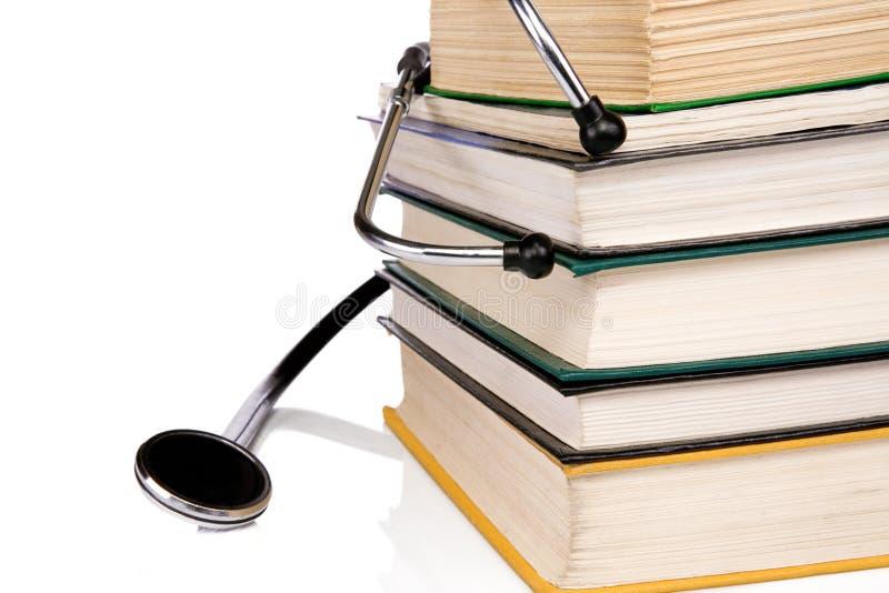 Pila de libros y de estetoscopio aislados en blanco imágenes de archivo libres de regalías