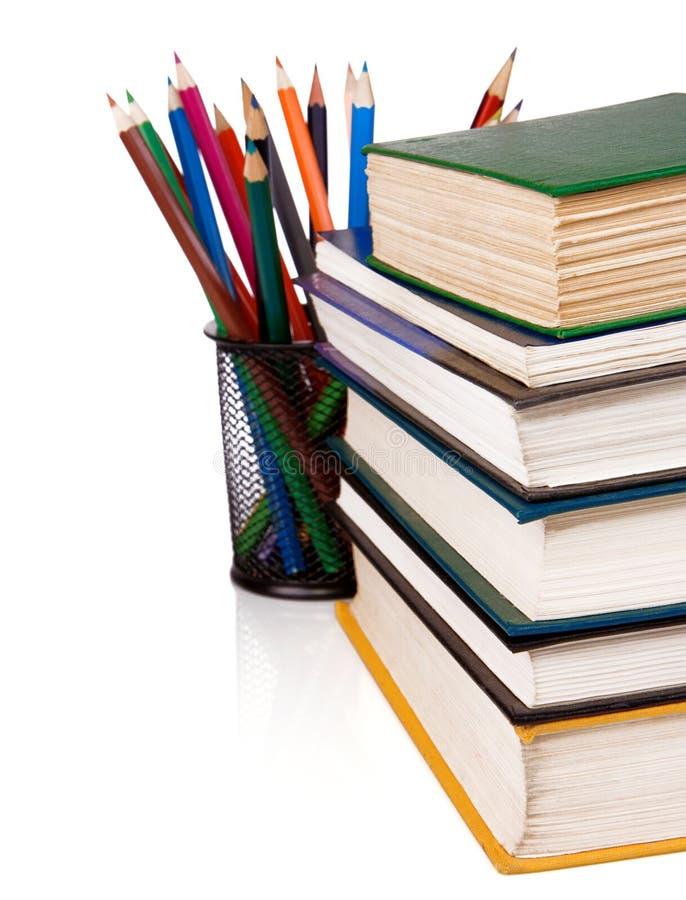 Pila de libros y de lápices aislados en blanco imagen de archivo libre de regalías