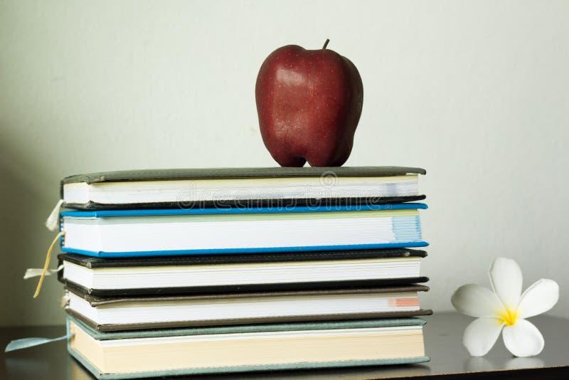 Pila de libros y de manzana roja imagen de archivo