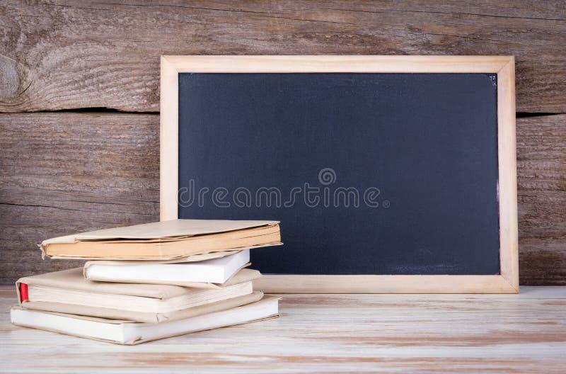 Pila de libros y de tablero de tiza en una tabla de madera fotos de archivo libres de regalías