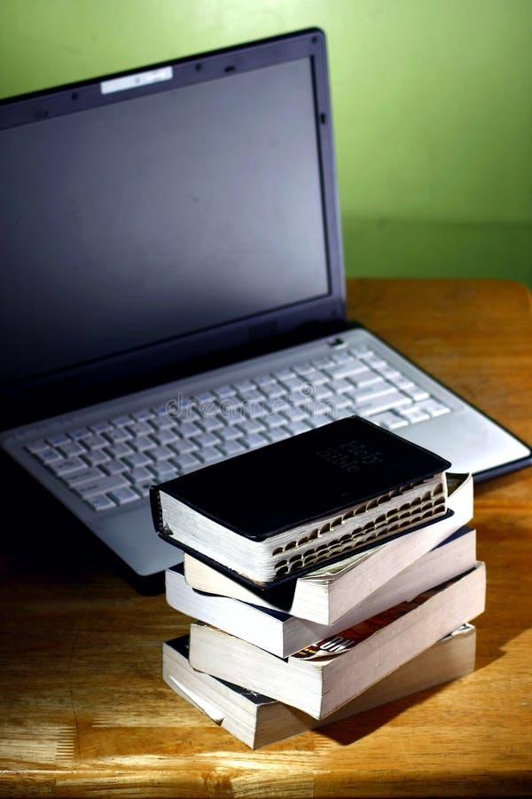 Pila de libros y de un ordenador portátil del ordenador foto de archivo libre de regalías