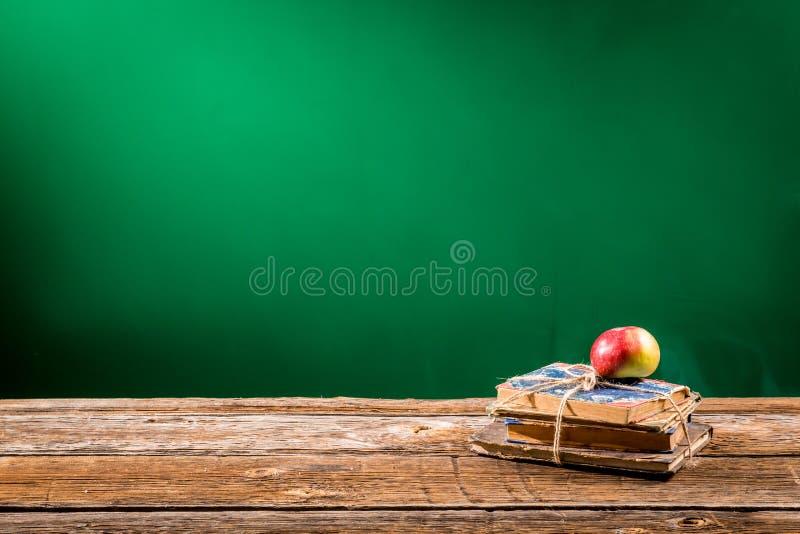 Pila de libros y una manzana en una sala de clase fotografía de archivo libre de regalías