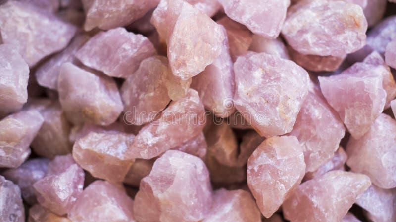 Pila de los cristales de cuarzo color de rosa sin pulir, aplicaciones semipreciosas de las piedras preciosas como decoración o en fotos de archivo