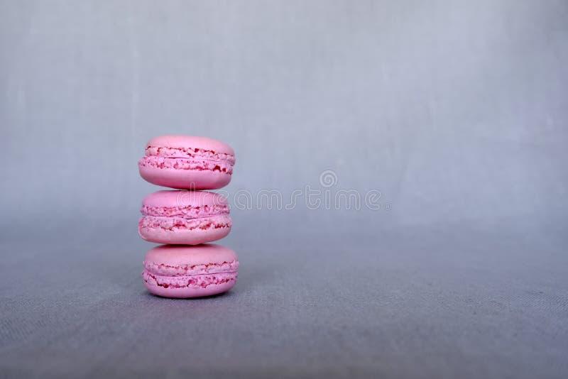 Pila de macarons rosados franceses deliciosos de la frambuesa en fondo gris con el espacio de la copia imágenes de archivo libres de regalías
