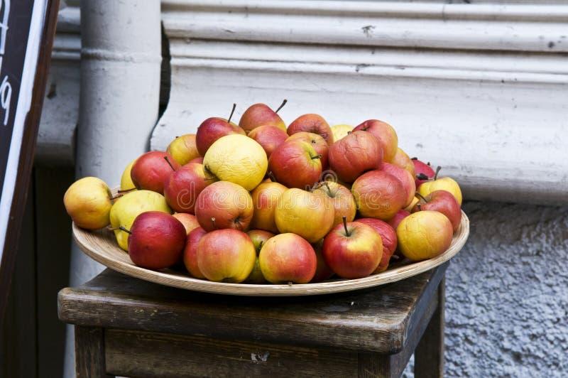 Pila de manzanas rojas y amarillas en plato foto de archivo
