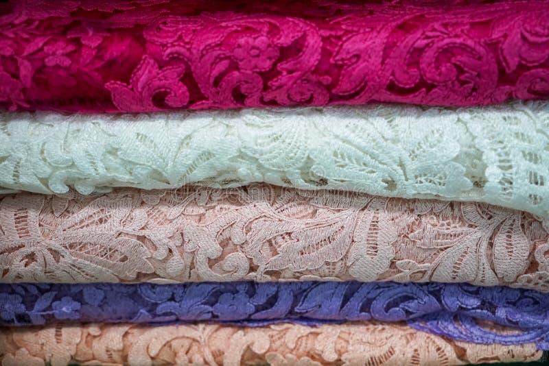 Pila de materia textil tradicional delicada de la tela del cordón en modelo natural en rosado, blanco, azul claro en la tienda lo fotos de archivo libres de regalías