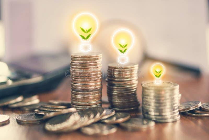 Pila de moneda con el árbol que crece en la bombilla, idea para el crecimiento del negocio imagenes de archivo