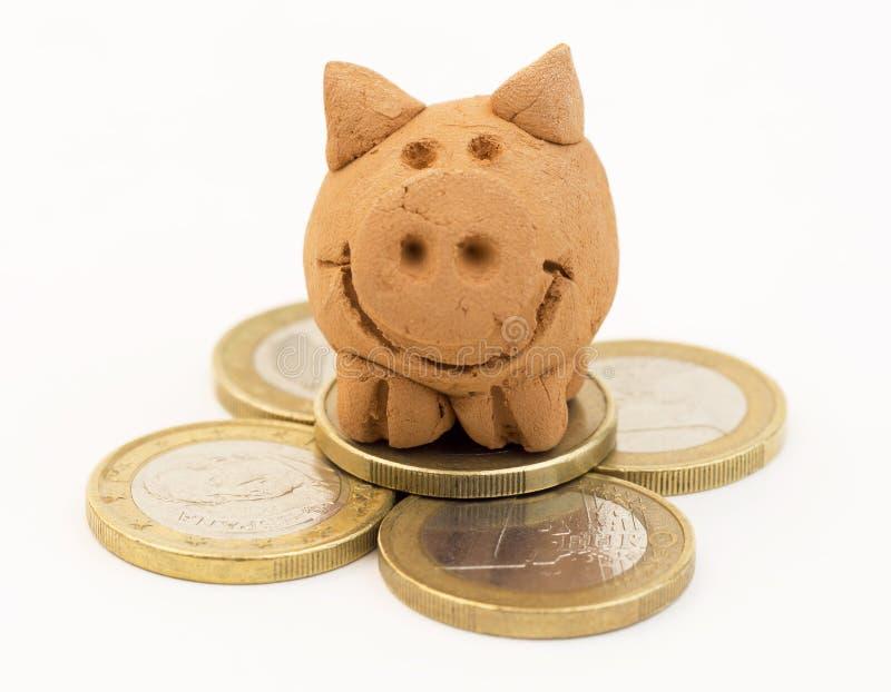 Pila de monedas con el pequeño juguete guarro foto de archivo