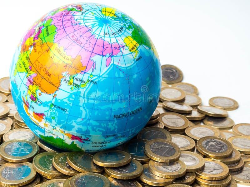 Pila de monedas con el planeta en el fondo - concepto del mundo de ahorrar el planeta, concepto de relación entre el dinero, econ imágenes de archivo libres de regalías