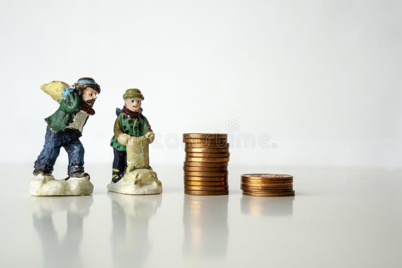 Pila de monedas con las figuras del trabajador en el funcionamiento blanco del fondo para el sueldo bajo del concepto de los peni foto de archivo