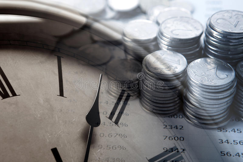 Pila de monedas con los dígitos y la cara de reloj imagen de archivo
