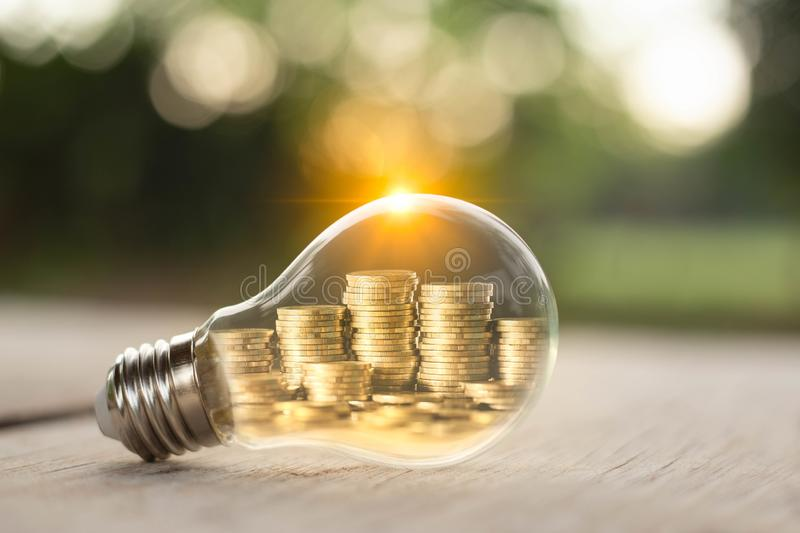 Pila de monedas dentro de una bombilla para el concepto del dinero de la reserva, ideas creativas de la planificación de empresas fotografía de archivo libre de regalías