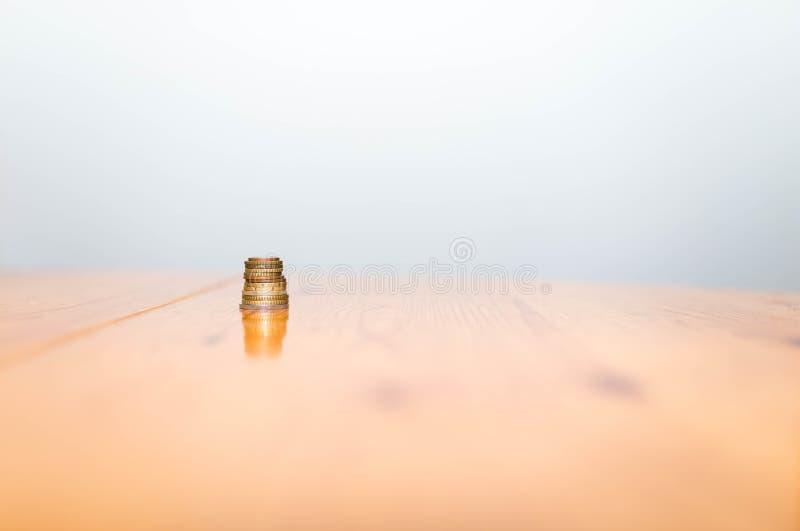 Pila de monedas en la tabla reflectora de madera de pino, imagen conceptual de la macroeconomía fotos de archivo