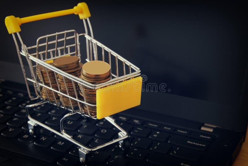 pila de monedas en una carretilla en un teclado del ordenador portátil haga el dinero o hacer compras concepto del comercio en lí fotografía de archivo libre de regalías