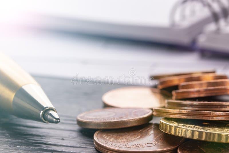 Pila de monedas euro euro en la tabla de madera negra vieja Pluma, cuaderno y documentos de contabilidad con números fotografía de archivo