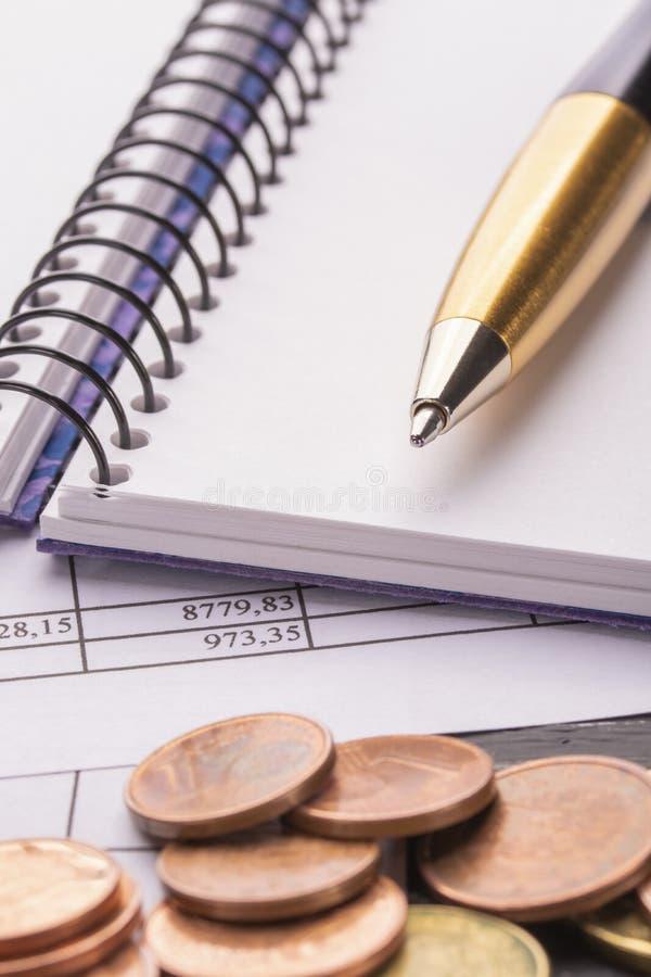 Pila de monedas euro euro en la tabla de madera negra vieja Pluma, cuaderno y documentos de contabilidad con números fotos de archivo libres de regalías