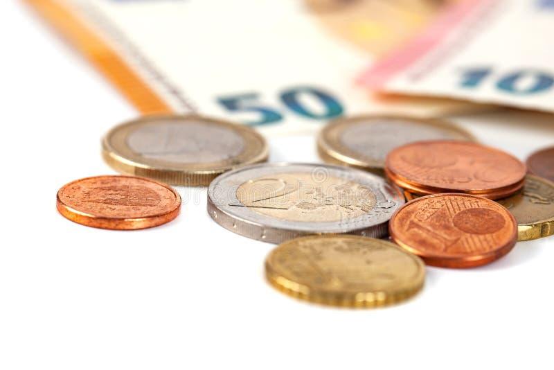 Pila de monedas euro y de billete de banco aislados en el fondo blanco fotos de archivo libres de regalías