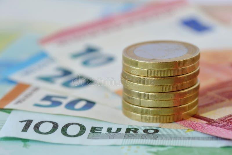 Pila de monedas y billetes de banco de 100, 50, 20 y 10 euros imágenes de archivo libres de regalías