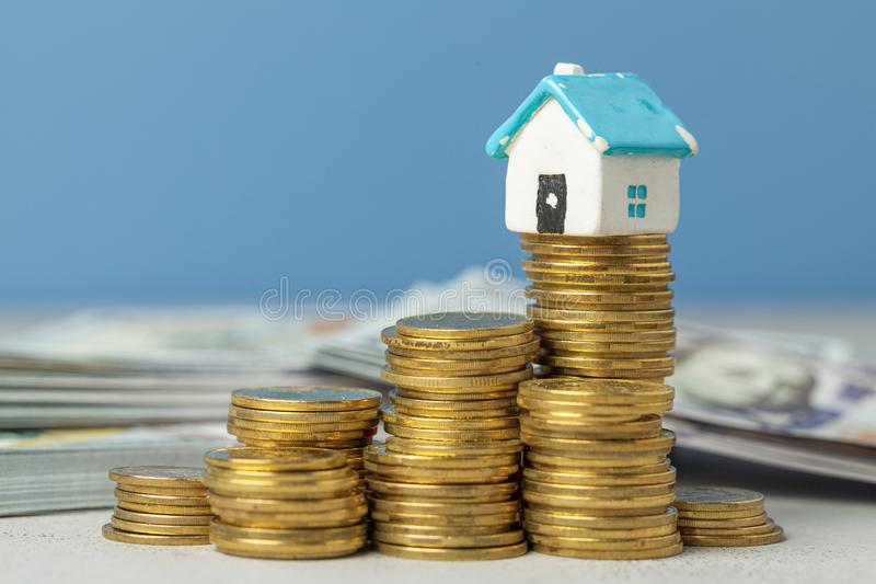 Pila de monedas y de una casa vieja Concepto de servicio de reparación casero costoso foto de archivo libre de regalías