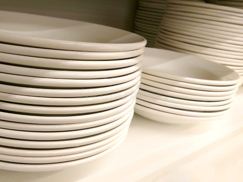 Pila de nuevos placas y cuencos llanos blancos limpios en el estante fotografía de archivo libre de regalías