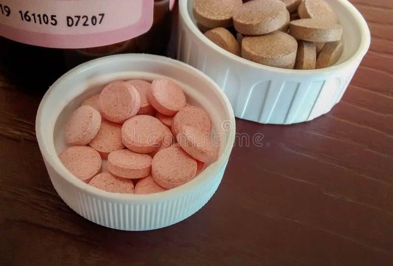 Pila de píldoras del hierro y de la vitamina b12 dentro de los casquillos de sus botellas imagen de archivo libre de regalías