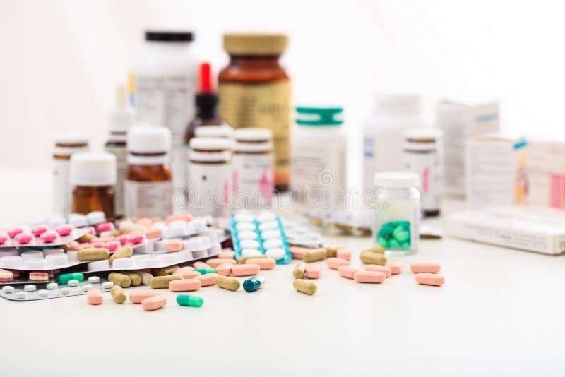 Pila de píldoras y de envases en el fondo blanco fotos de archivo