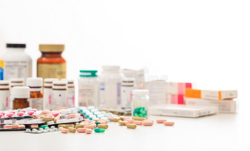 Pila de píldoras y de envases en el fondo blanco imagen de archivo