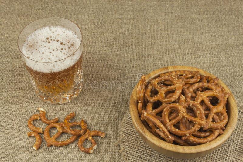 Pila de palillos del pretzel Entretenimiento para ver la TV Cerveza en un vidrio en la tabla fotos de archivo libres de regalías