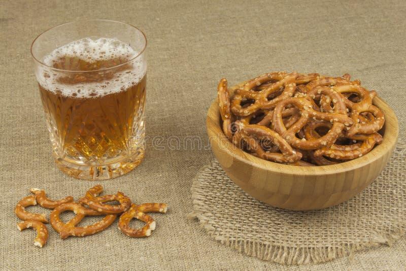 Pila de palillos del pretzel Entretenimiento para ver la TV Cerveza en un vidrio en la tabla imagenes de archivo
